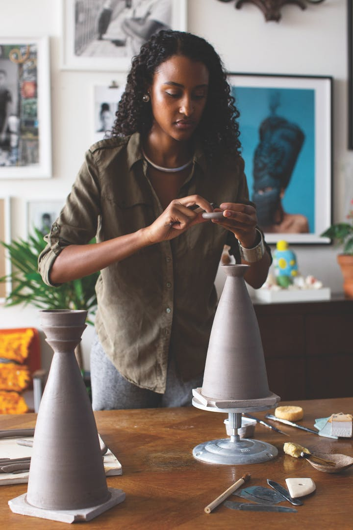 Dina Nur Satti in studio shaping clay for two tall slim ceramic vessels