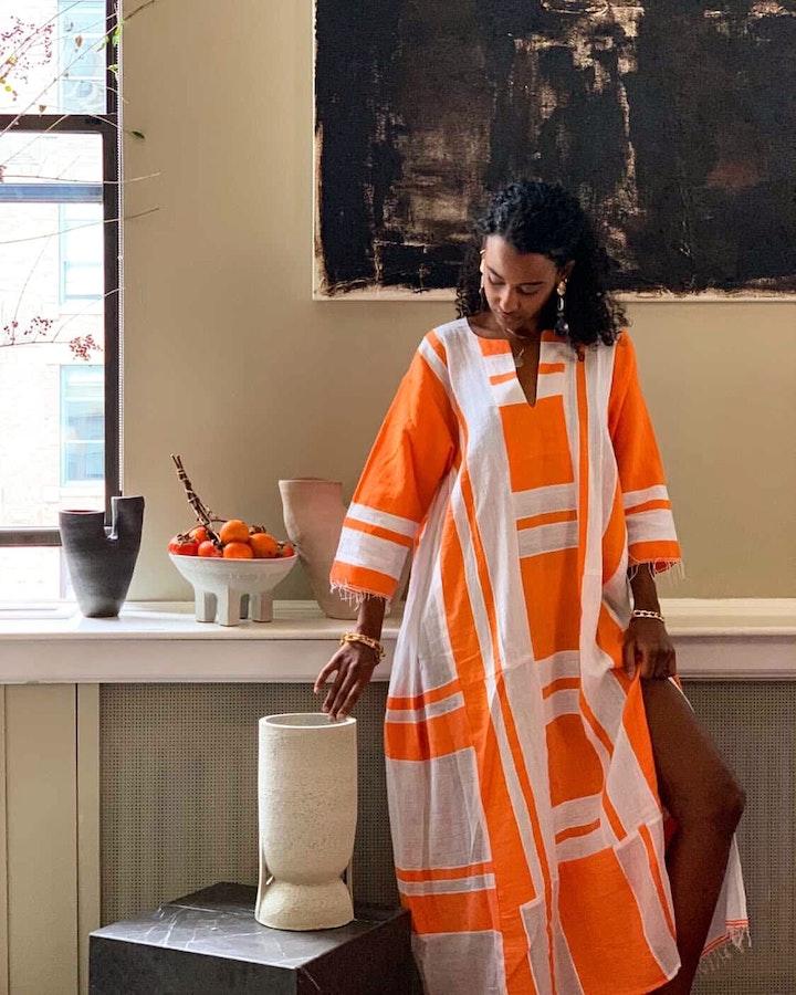 dina nur satti wearing a bright orange and white dress posing with various ceramic vessles