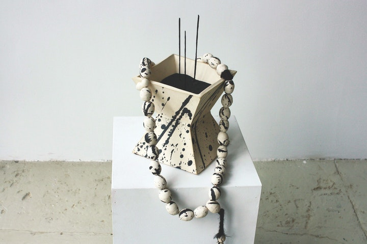 White ceramic incense burner with black splattered detail arranged with matching ceramic bead necklace