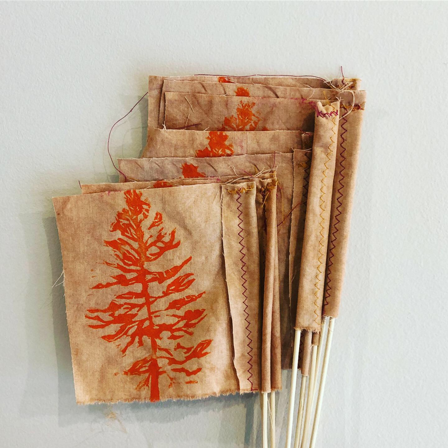 Flags made from dyed tan fabric sewn to wooden sticks. The fabric flags have an orange image of a tree printed on them.