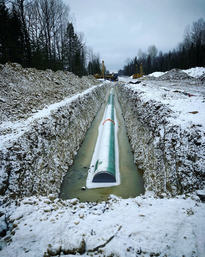 A pipeline construction site in winter flanked by a forest. In a deep ditch in the snowy earth lies a large frosty pipe half submerged in murky water.
