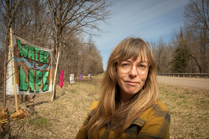 Portrait of a woman in a plaid shirt standing in the ditch beside a rural road with a handmade fabric sign hanging against the treeline that says water is life