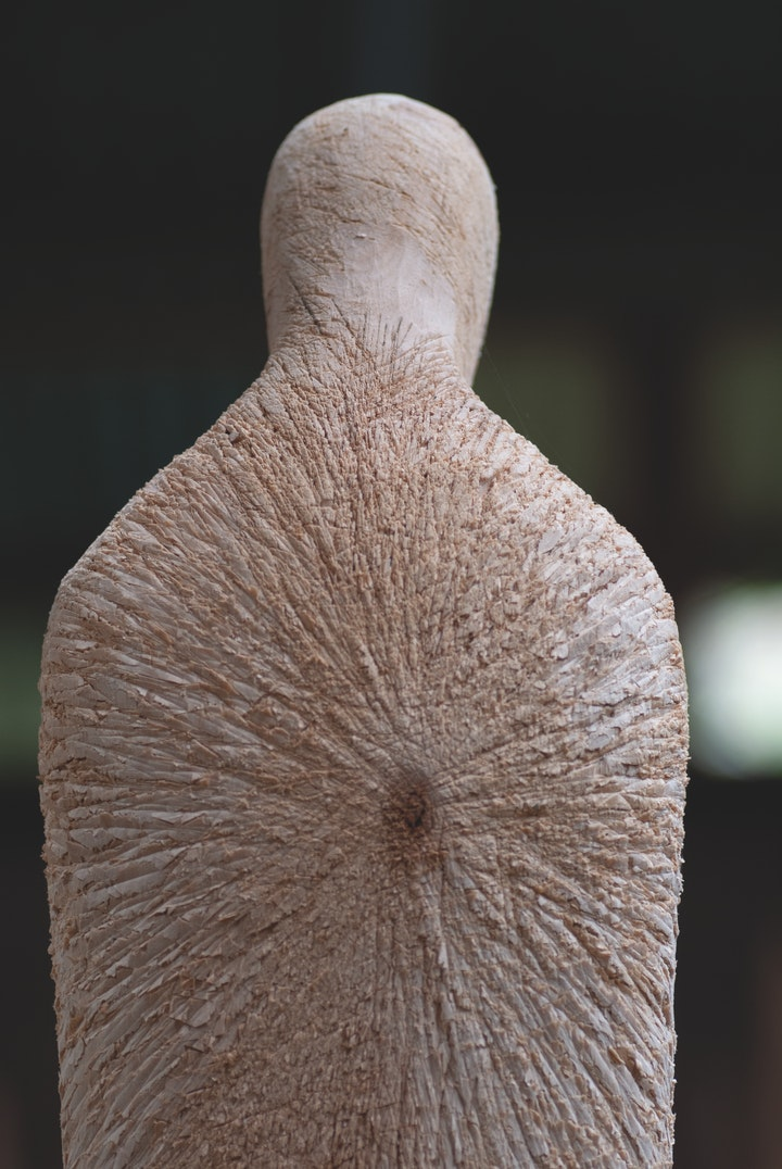 A large humanoid wooden figure viewed from behind. It's head is bowed and its back and shoulders are rough with many long cuts radiating from its center.