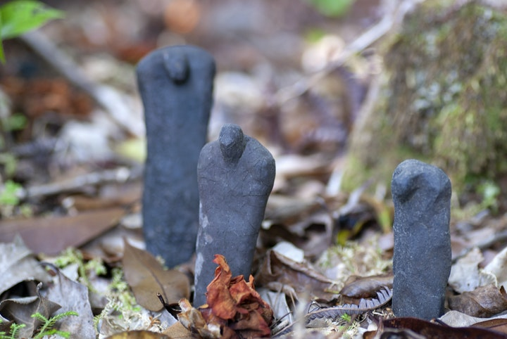 Three small humanoid figures carved from dark gray stone arranged among moss and leaves beside a tree.