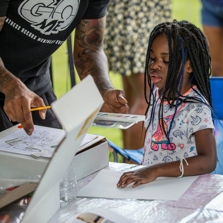 A student learning about the activities in the Take Home Craft | Atlanta kit at an outdoor pop-up event