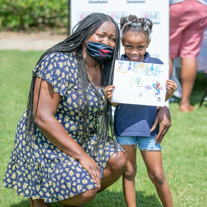 A student showing off her artwork beside an activity leader at an outdoor pop-up event