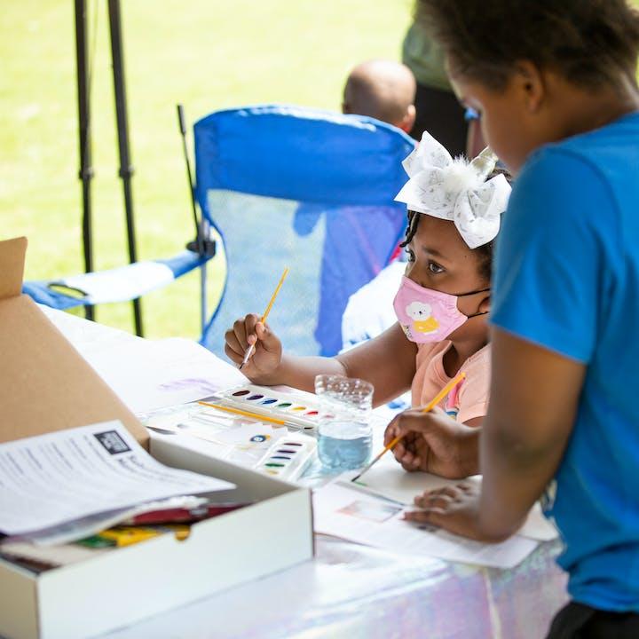 Students painting using supplies from the Take Home Craft | Atlanta kit at an outdoor pop-up event