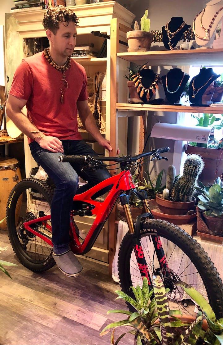 Derek Mirbilio on a bike beside his jewelry