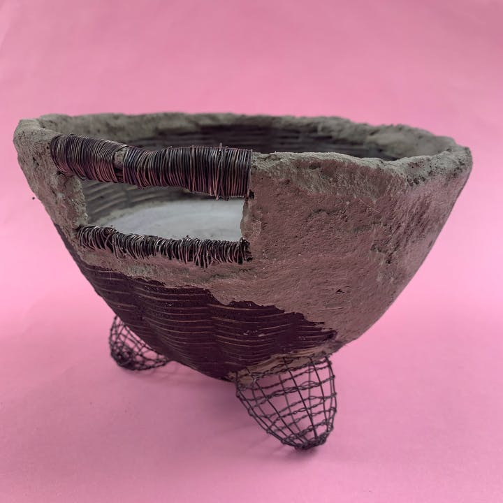 Woven sculptural basket with cement and pink background
