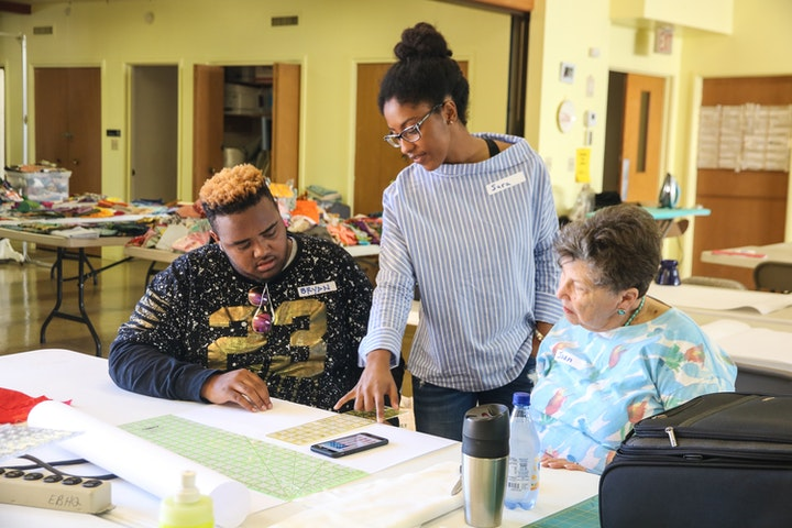 Three people working together at a table on a quilting project the middle person standing and pointing at a design