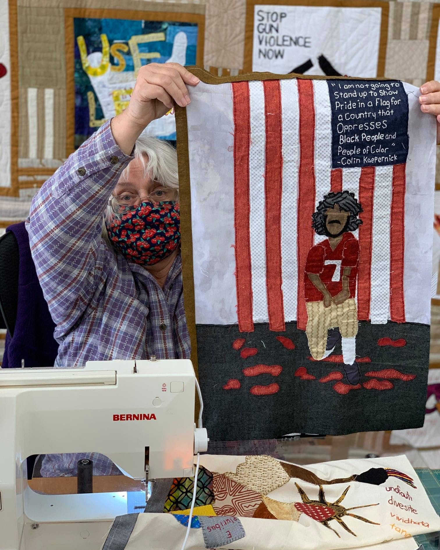 Person at a sewing machine holding up quilt project