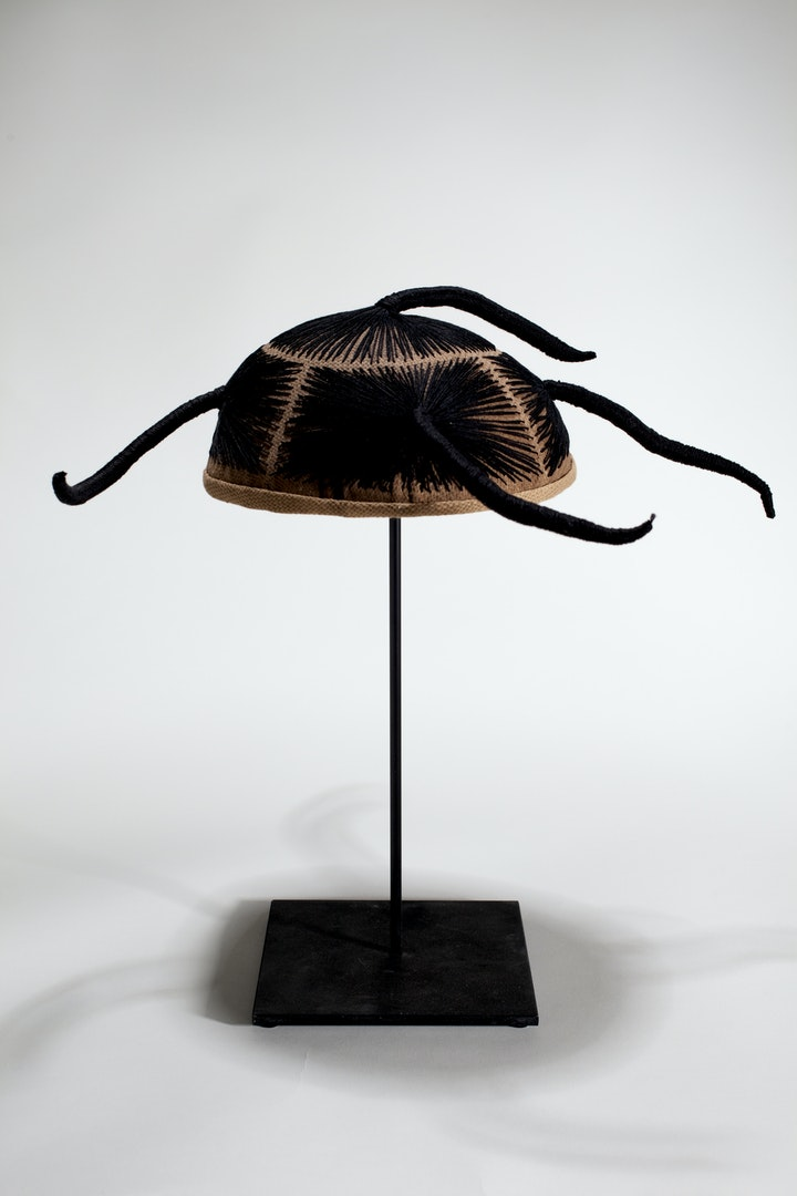 Wig with four tight braids on a stand