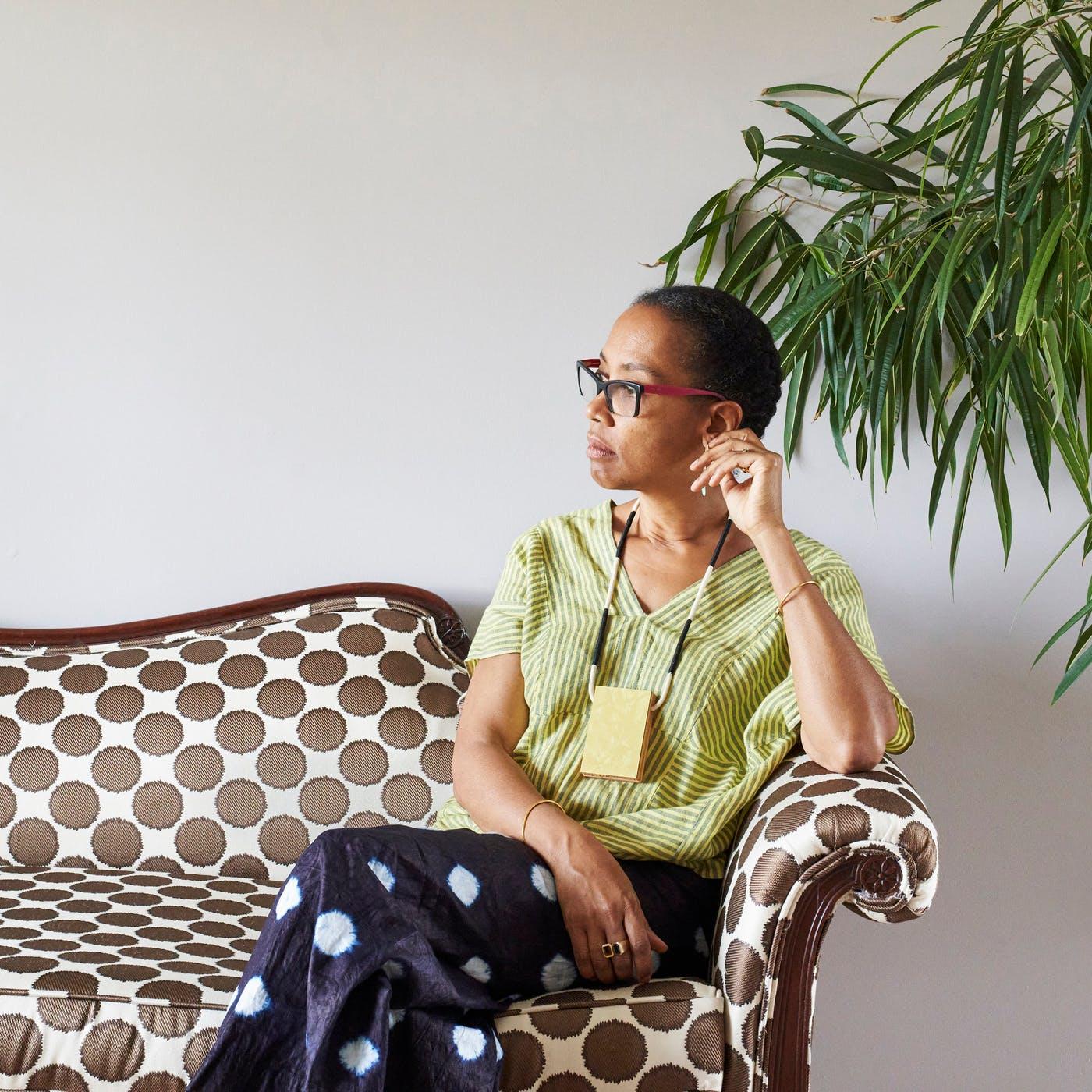 Photo of artist Sonya Clark on sofa beside a houseplant