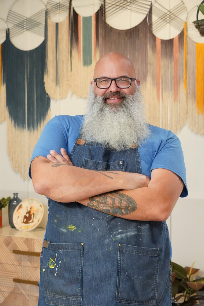Portrait of bearded bald man with blue t-shirt glasses and apron smiling with arms folded