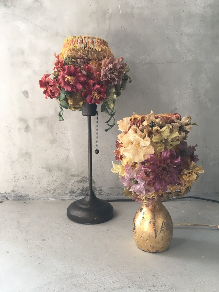 Two table lamps with agar flower-adorned shades in a arranged beside a concrete wall