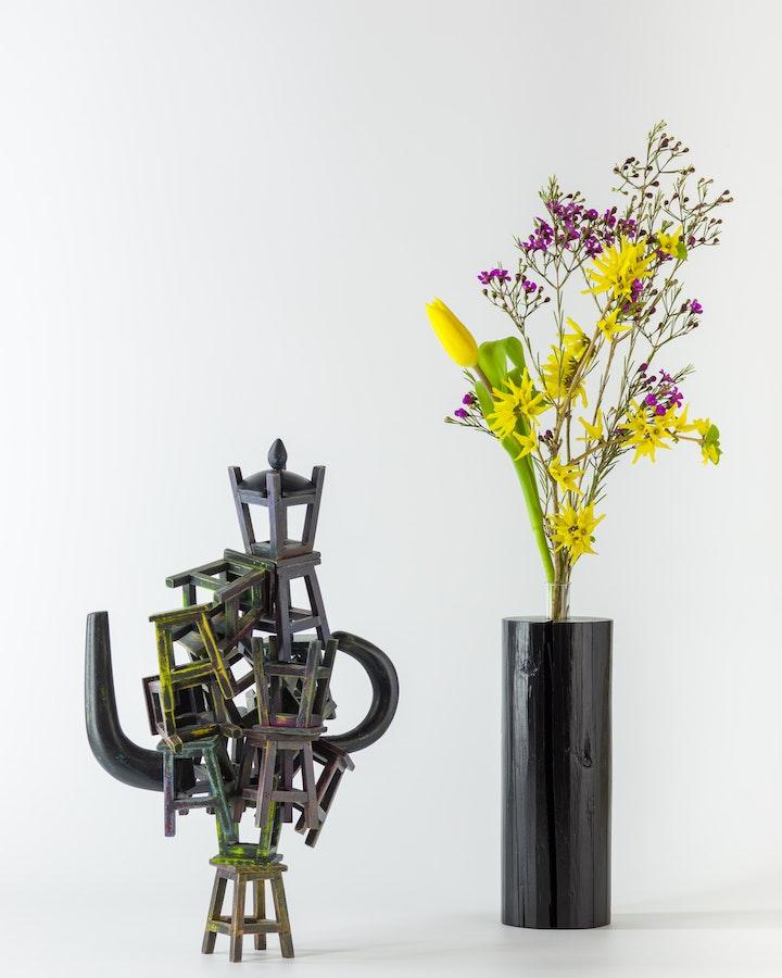 Black wooden vase with flower arrangement beside wooden sculpture