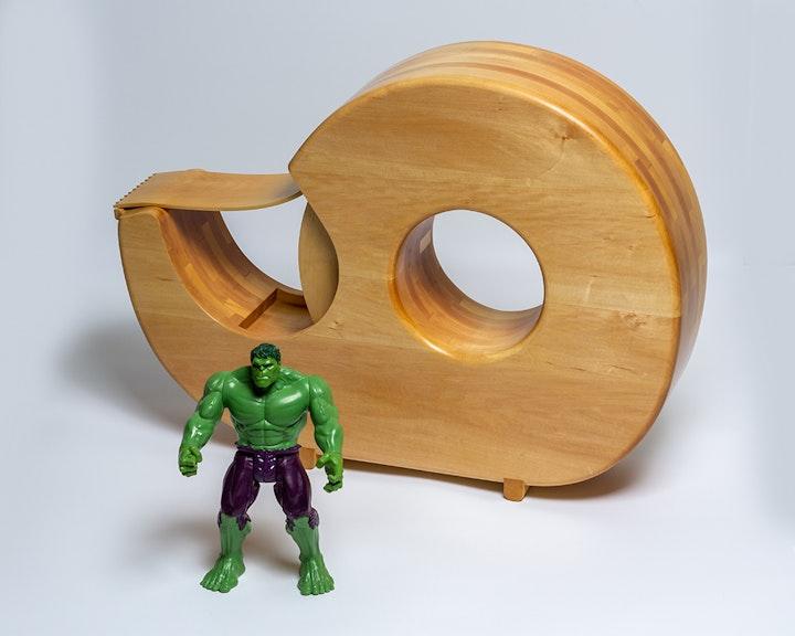 Wooden sculpture of a tape dispenser beside figurine of The Hulk
