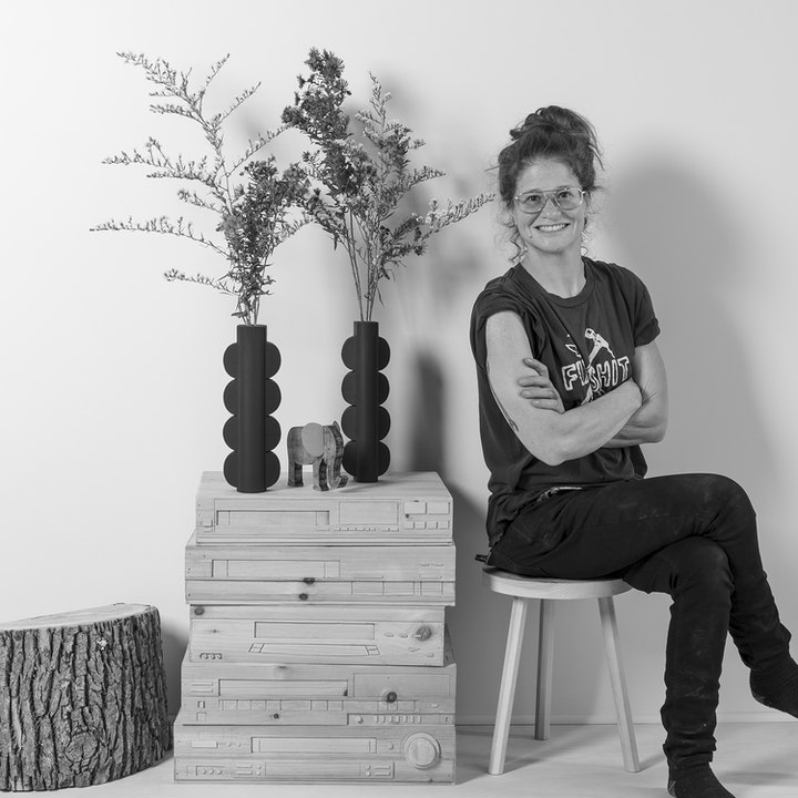 Grayscale ortrait of smiling artist sitting with crossed arms beside sculptural wooden furniture peices