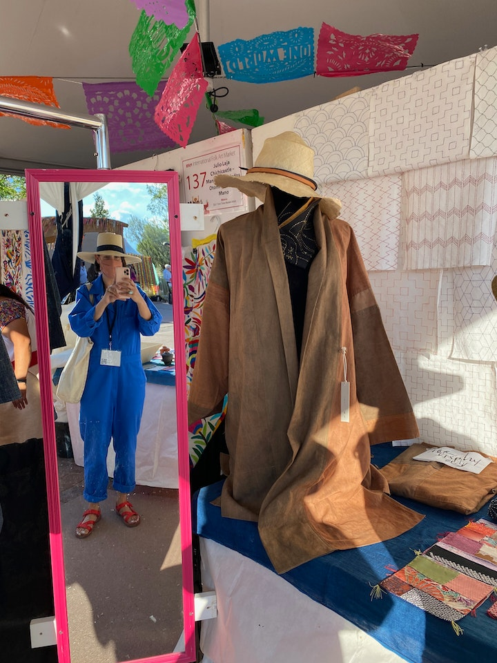 Self portrait of person in mirror wearing blue jumpsuit hat and facecovering and craft booth