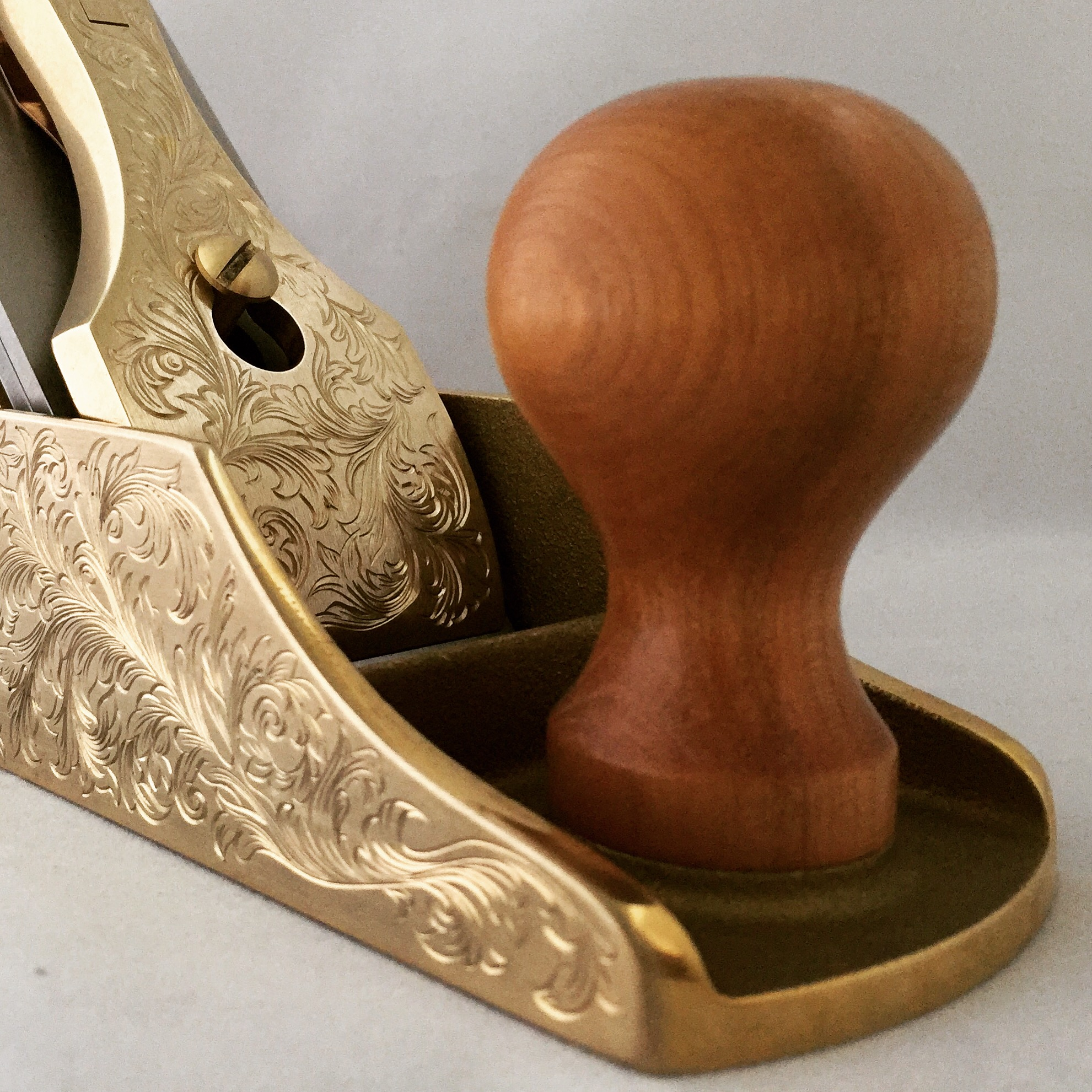 Closeup of gold handplane with ornate floral engravings
