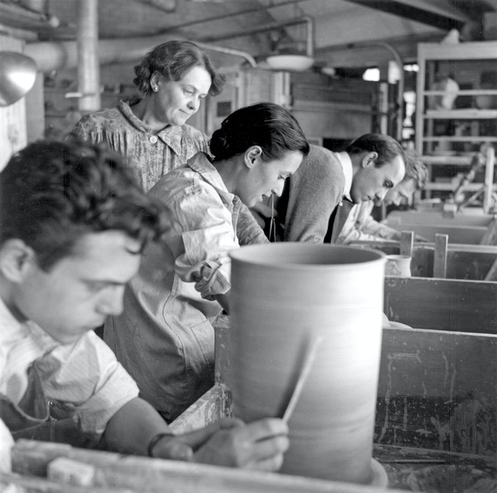 Black and white photo of instructor with students at work in a ceramics studio