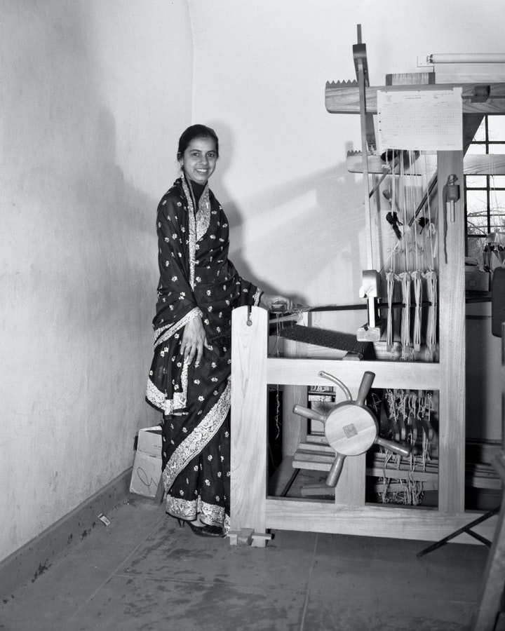 Black and white photo of textile artist in Indian dress posing beside large wooden loom