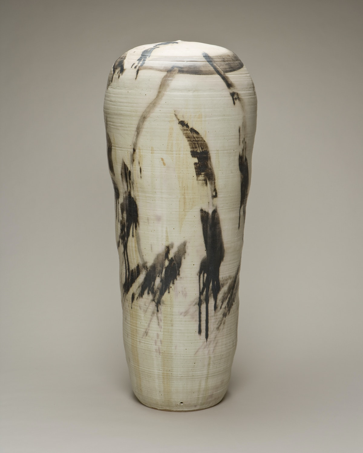 Light colored tall cylindrical stoneware vessel with darker leaflife details