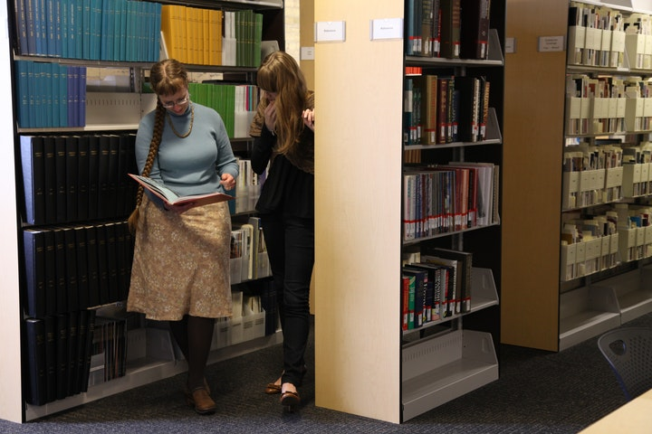 two researchers looking at a book together in library stacks
