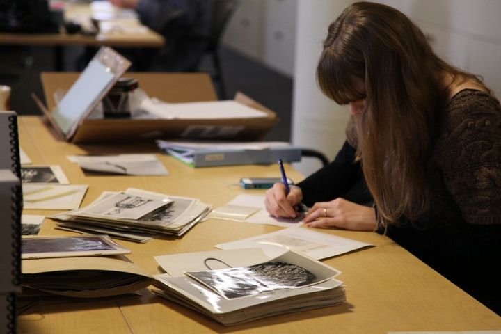 researcher in a library studying black and white photos on a desk