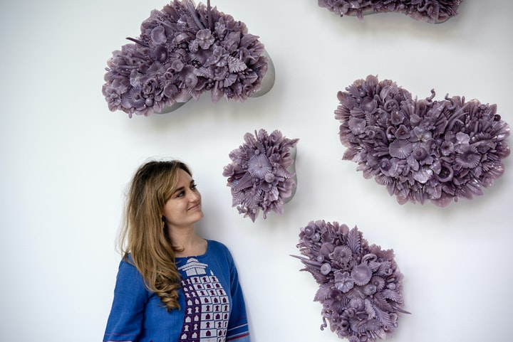 portrait of artist looking up at a series o wall sculptures that look like bunches of flower pedals made from purple glass all hanging on a white wall
