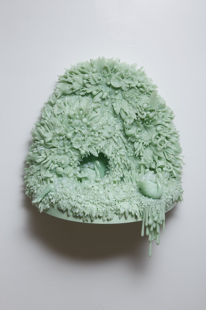 egg shaped wall sculpture made from countless mint green glass leaves and pedals with two swans moving through a bubbly tunnel mounted on a gray wall