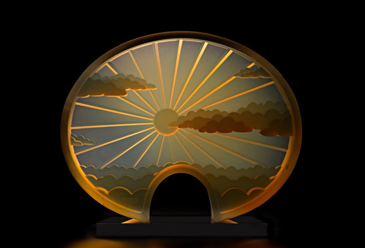 glass object depicting a sun shining through clouds and refracting subtle warm hues