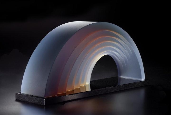 rainbow shaped glass object refracting subtle warm hues