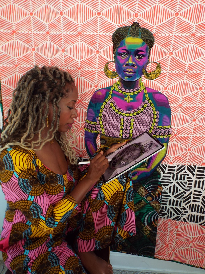 artist in vibrant pink yellow and blue dress sketching on a tablet beside a quilting a women in vibrant colors