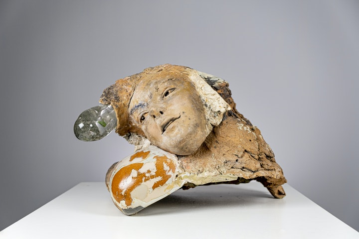 ceramic sculpture of weathered tan face looking askew and melded with amorphous clay and glass shapes on a white table gray background