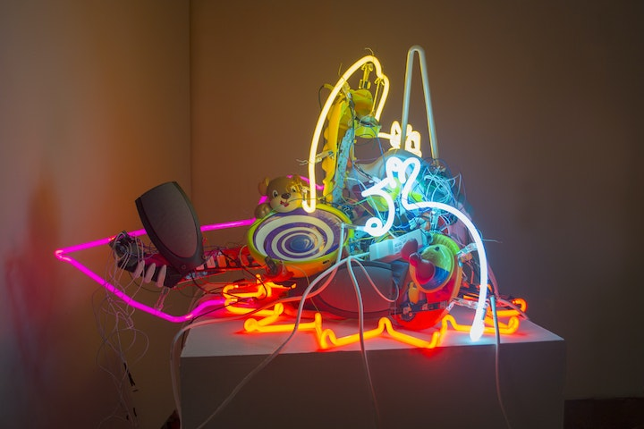sculpture with chaotic arrangement of glowing neon glass shapes and various electronic equipment and toys