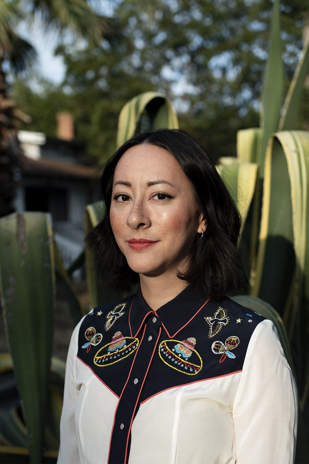 portrait of sun-illuminated person in a white and black embroidered western shirt posed infront of a large cactus in a yard with palm tree in background