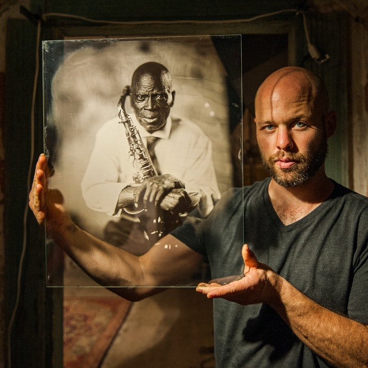photographer with shaved head and beard holding up an ambrotype portrait of a person with a saxophone