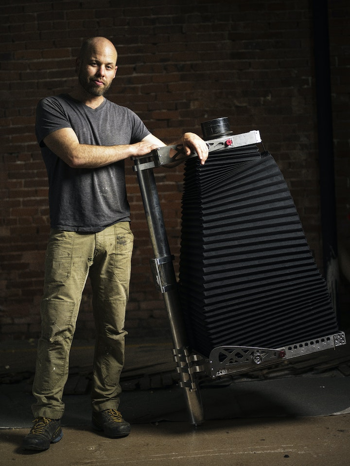 photgrapher in charcoal tshirt and olive pants posing with a large format view camera