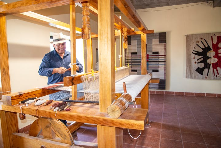 textile artist at a traditional loom