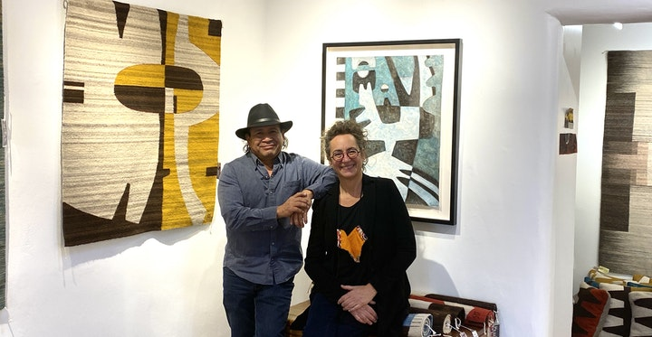 two artists posing in their studio with weavings and symbolist paintings hanging on the walls