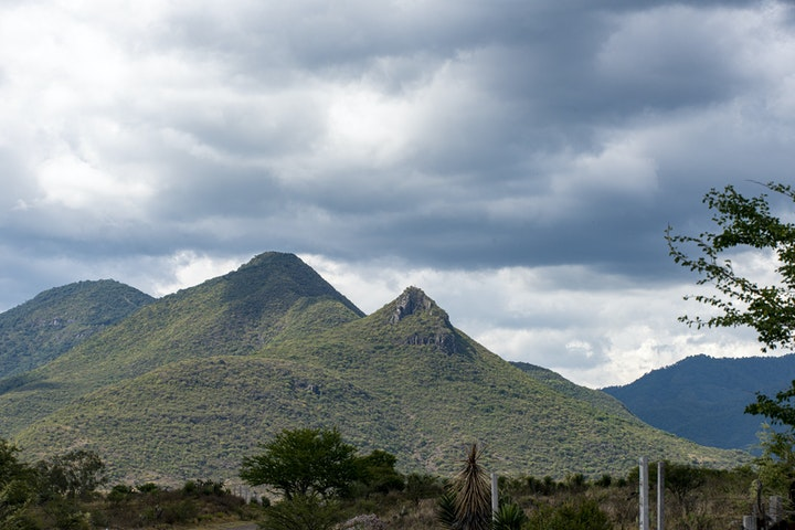 landscape photograph of a green mountain with cloudy sky