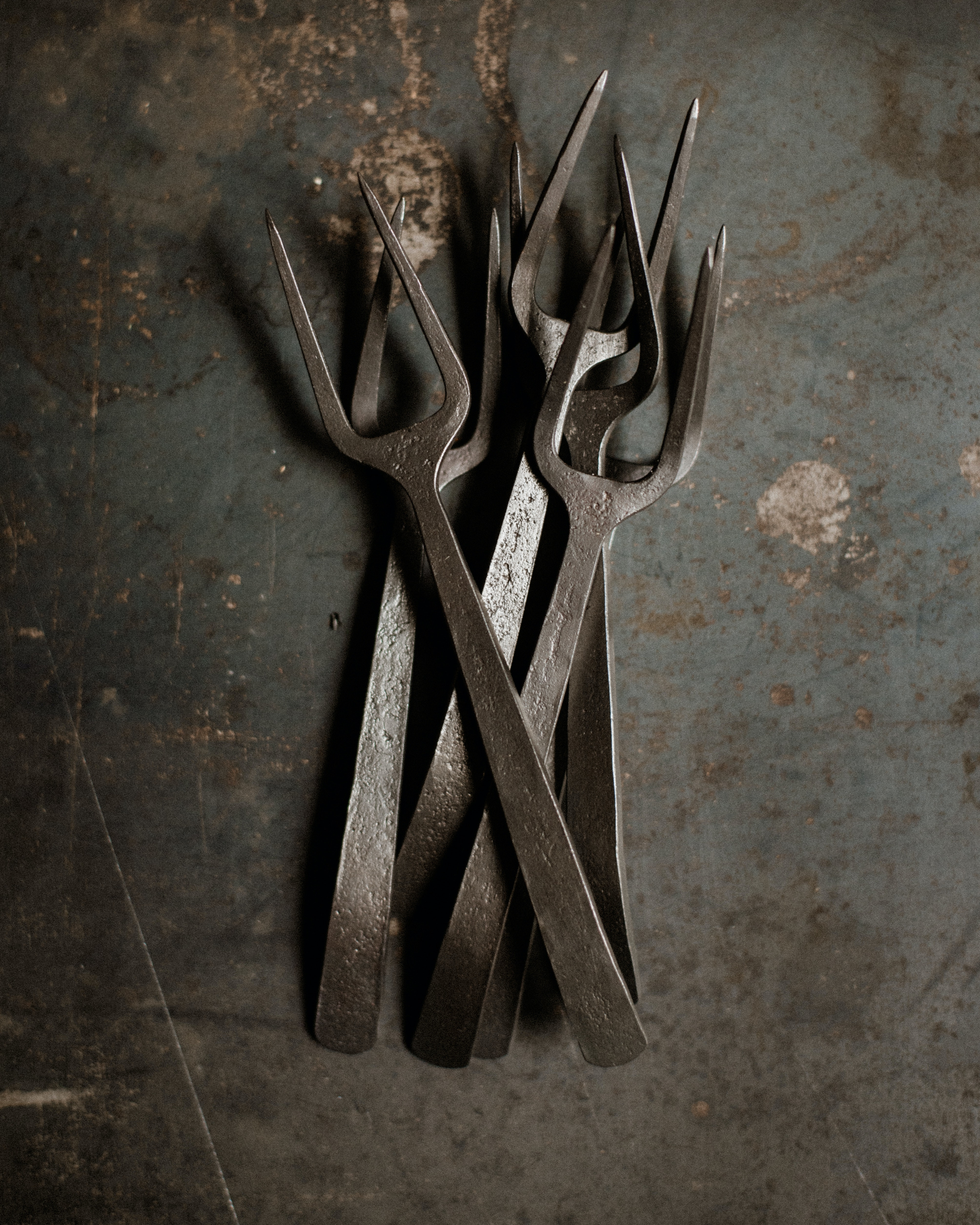 Set of handmade two pronged iron appetizer forks on industrial gray background