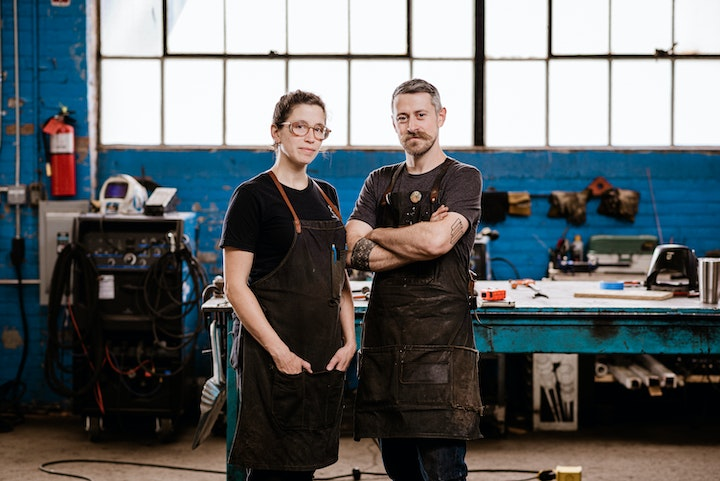 portrait of two blacksmiths wearing aprons posing in a shop with blue painted brick walls