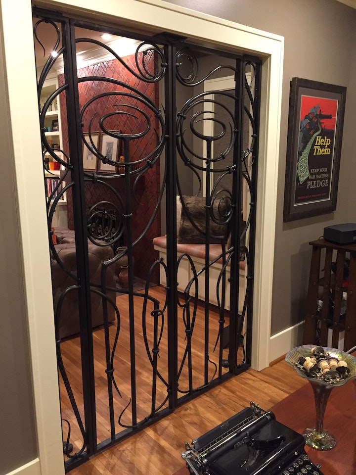 iron gate with swirling bars separating two rooms in a home