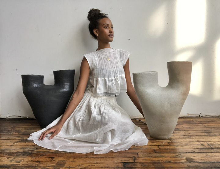 Woman in white dress kneeling on a wooden floor between two large ceramic vessels. One vessel is black and the other is white. She gazes off into the distance.