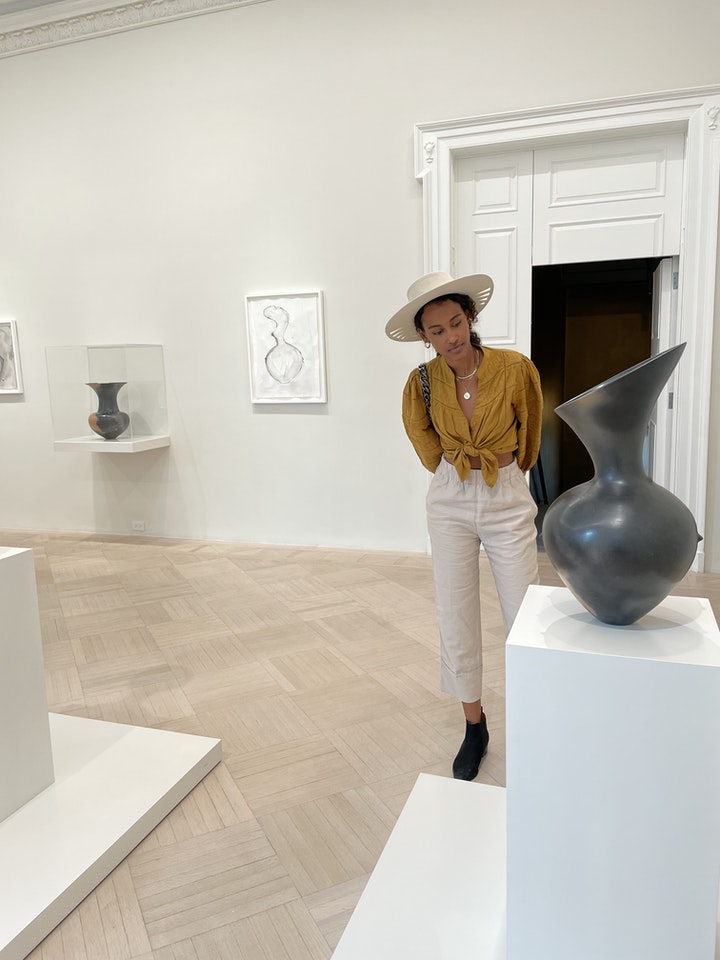 A woman studying a ceramic vessel on a white pedestal in an exhibtion gallery
