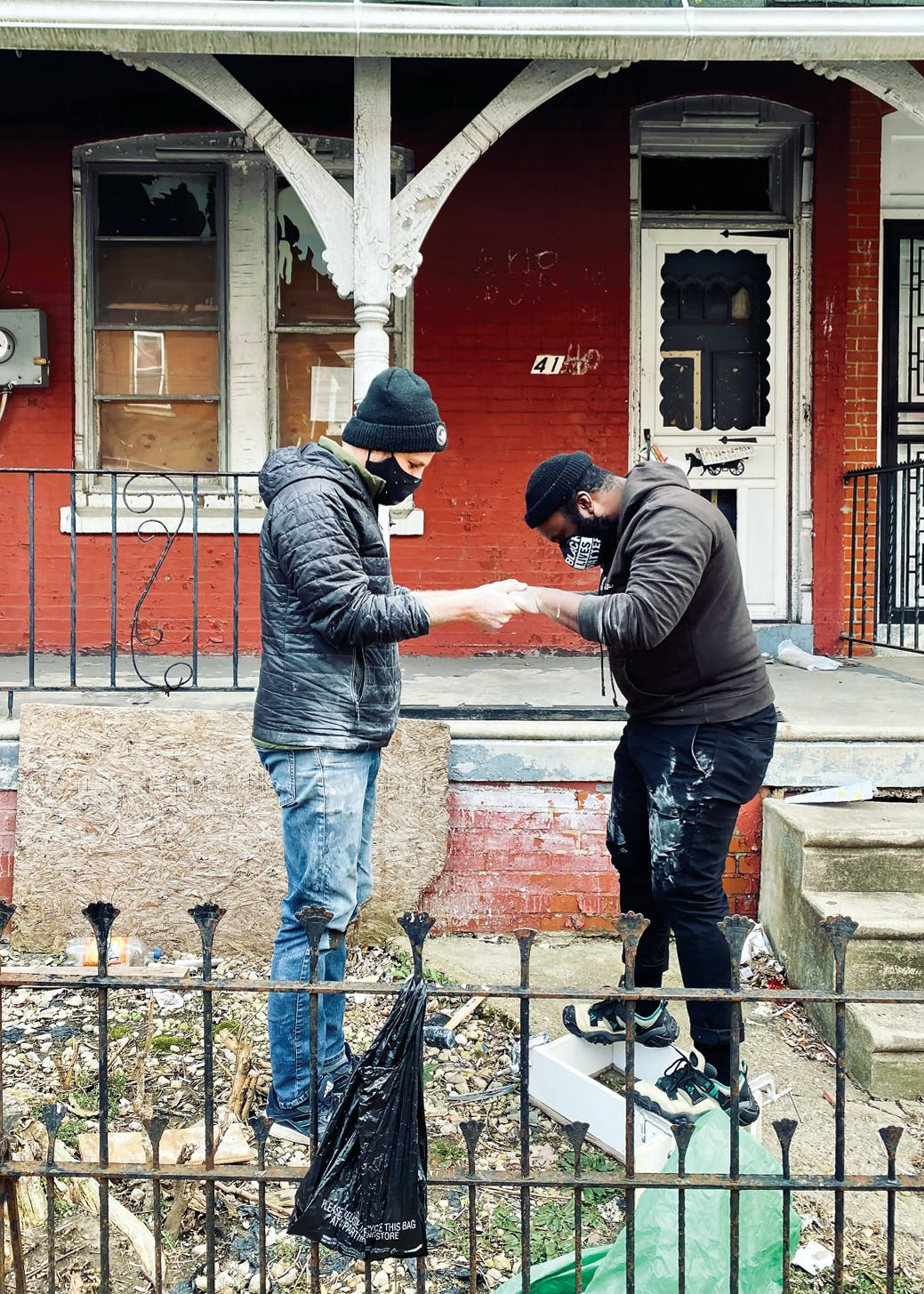 two people in face masks and jackets working together on a project in a yard outside a brick building