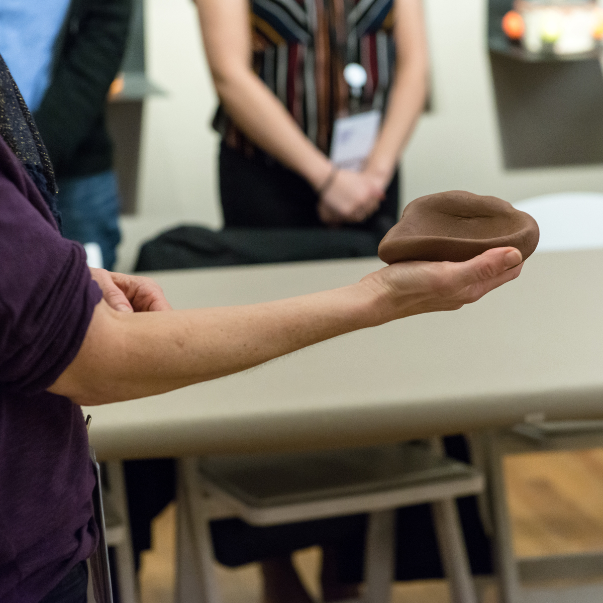 Person holding a wad of clay shaped like a rough bowl