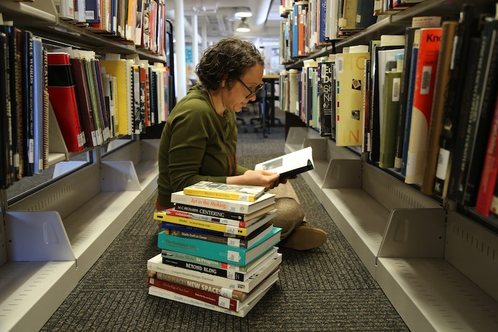 Person sitting on crosslegged in an aisle of a library with a stack of books